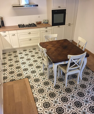 Old cement tiles in kitchen floor in London by Cimenterie de la Tour